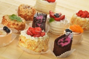 16279231-small-cakes-with-cream-and-berries-on-bamboo-table-cloth