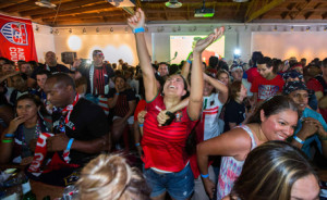 Portugal soccer fan, surrounded by USA fans, cheers for Portugal's second goal during the 2014 World Cup Group G soccer match between Portugal and the U.S. at a viewing party in Los Angeles