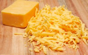 Grated mature cheddar cheese on wooden board